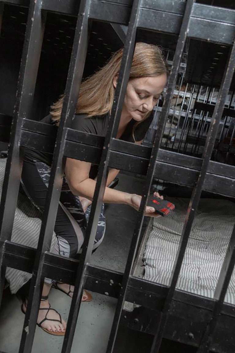 guest sitting inside St. Augustine Old Jail cell while holding an EMF meter