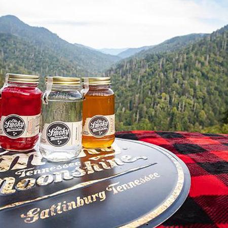 Ole Smoky Distillery moonshine bottles sitting on top of a surface with mountains in the background