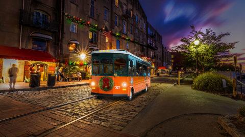 Savannah trolley driving past river street at night