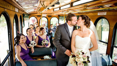 wedding couple kissing inside trolley while wedding party sits in the background